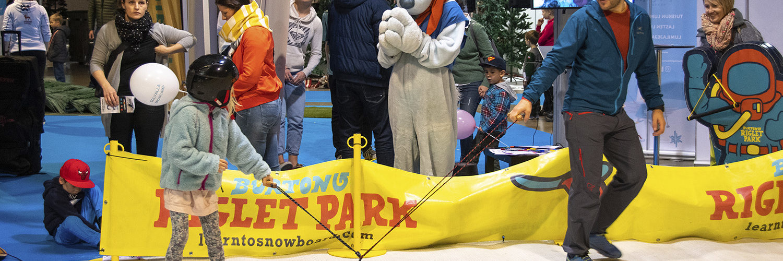 Suomen Hiihtokeskusyhdistyksen ja Suomen lumilautaliiton yhteisosastolla lapset pääsevät ottamaan tuntumaan lumilautailuun.